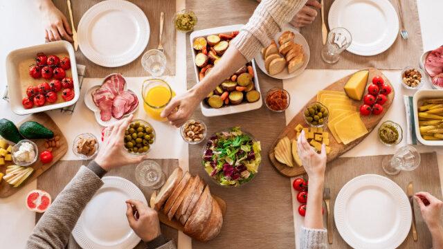 4人で食事のテーブルを囲む