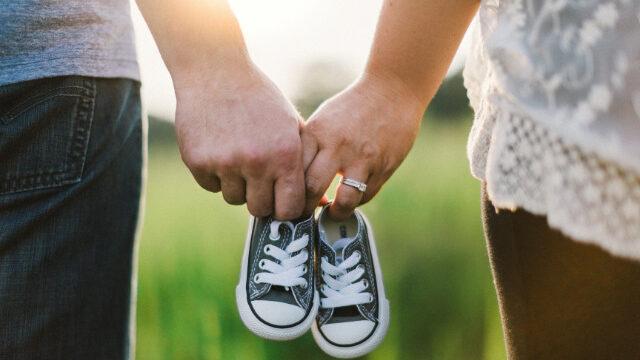 赤ちゃん用の靴を持つ夫婦の後ろ姿
