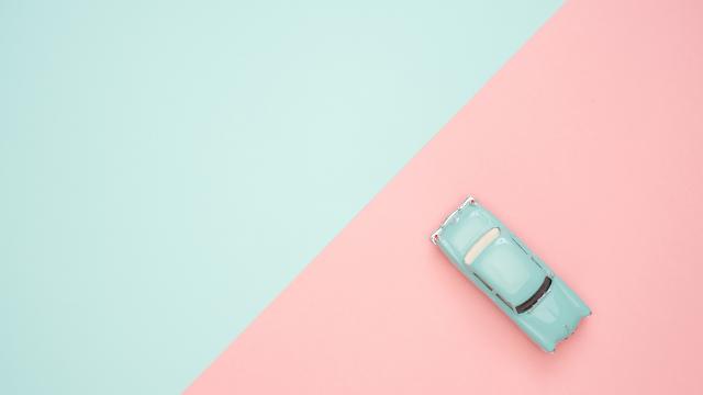 青とピンクの床の上に置いてある青いミニカー