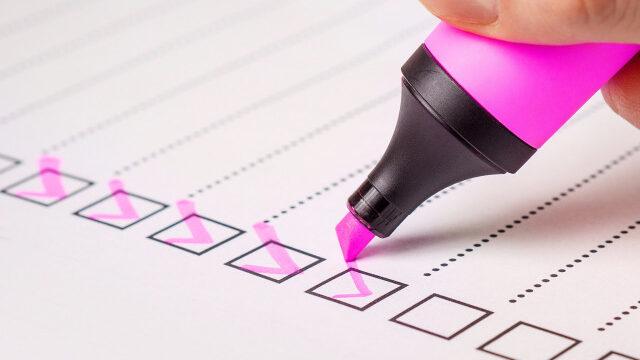 ピンクの蛍光ペンでチェックリストにチェックを入れる