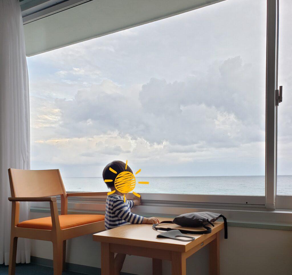 オーシャンビューの窓から外を見る子供