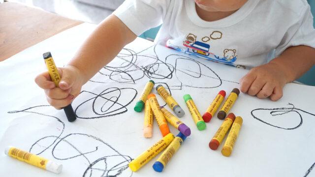 色とりどりのクレヨンと落書きする子供