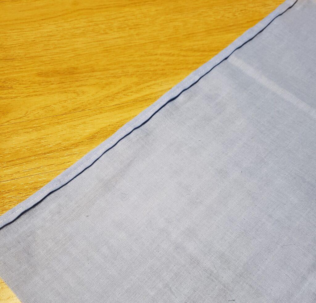 3つ折りして端を縫ってある水色の生地