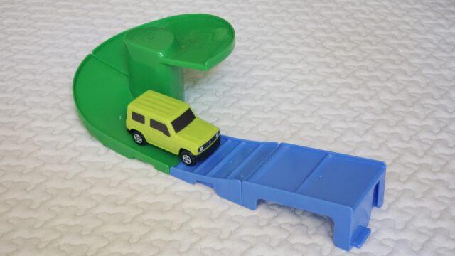 オモチャの道路を走る緑のミニカー
