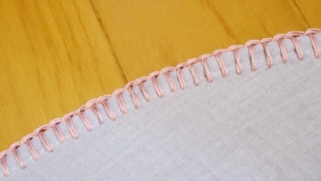 水色のガーゼ生地にピンクの糸でブランケットステッチ