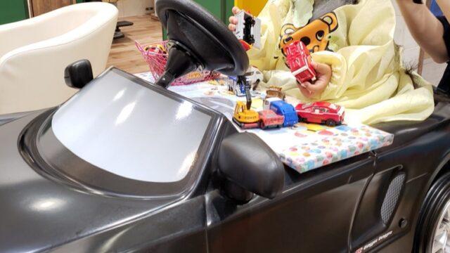 黒い車型カット椅子とおもちゃの車